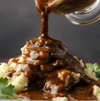 Vegan gravy pouring from a glass jug onto mashed potatoes