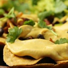 Vegan nacho cheese drizzled over tortilla chips