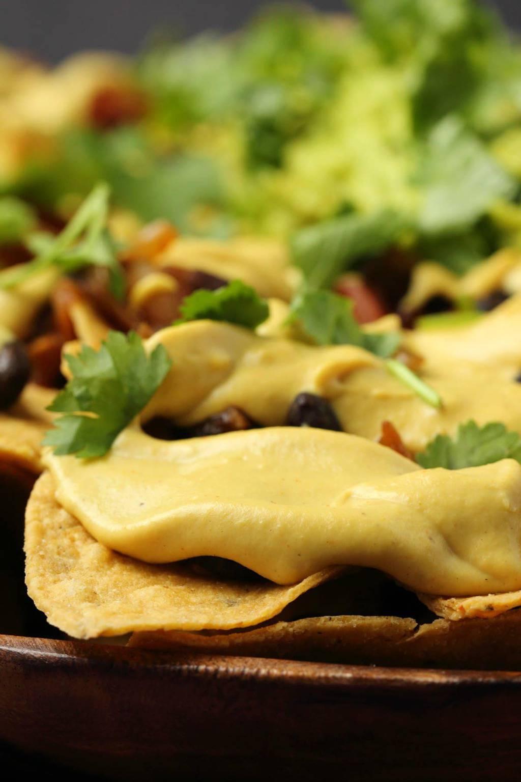 Vegan nacho cheese poured over nachos.
