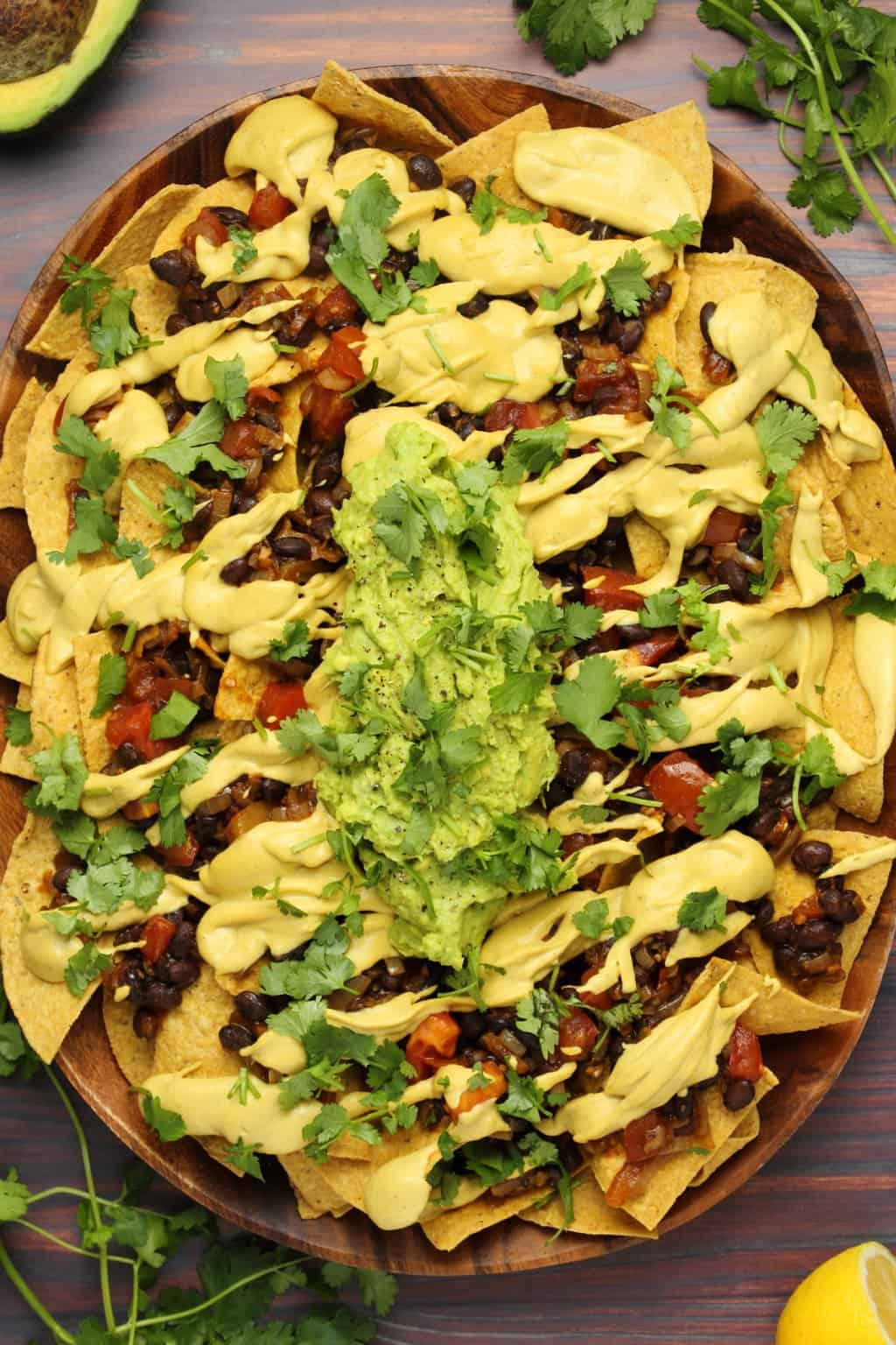 Vegan nacho cheese poured over fully loaded nachos with black beans, salsa and guacamole.