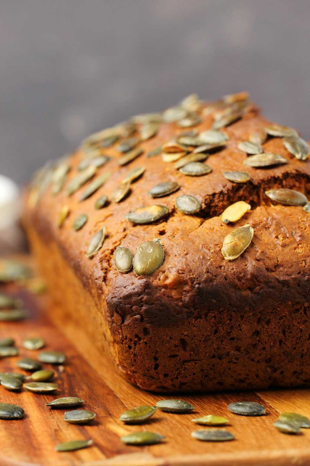 Vegan pumpkin bread topped with pumpkin seeds on a wooden board.