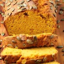 Sliced loaf of vegan pumpkin bread on a wooden board.