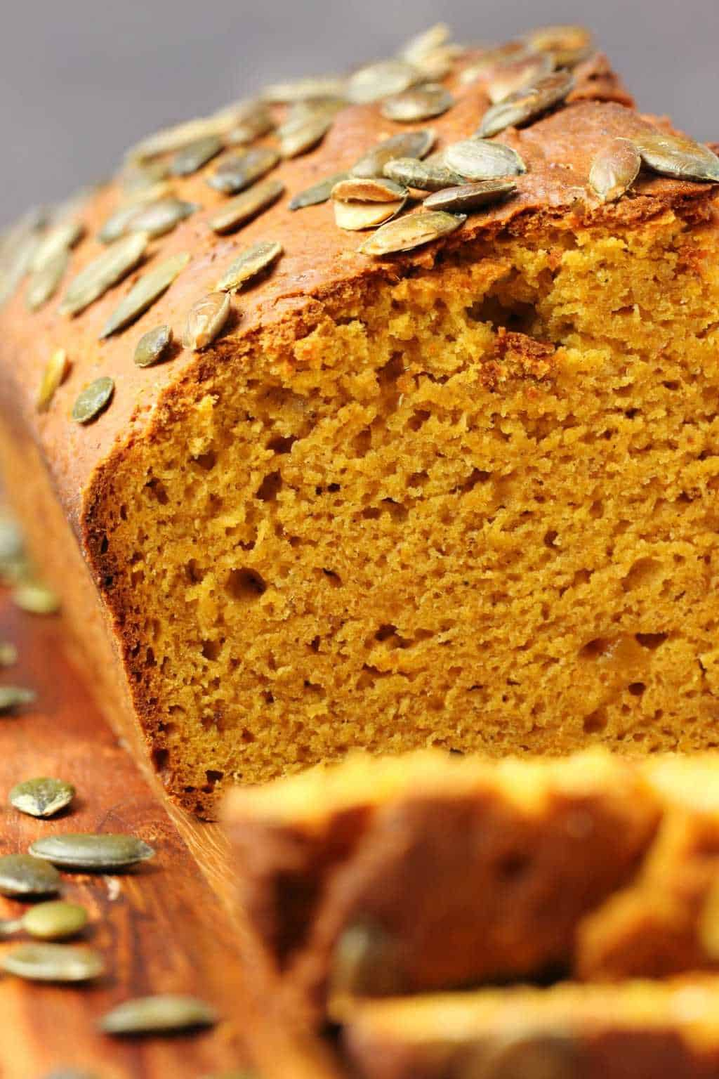 Sliced vegan pumpkin bread on a wooden board.
