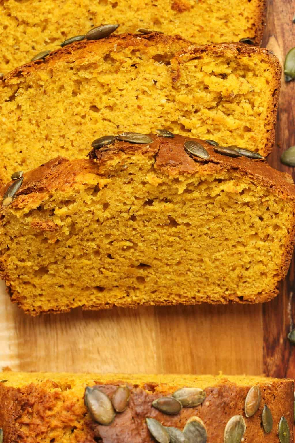Slices of vegan pumpkin bread on a wooden board.