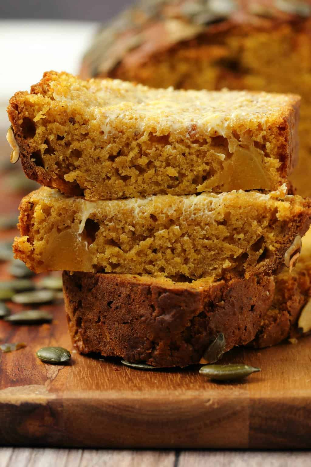 Slices of vegan pumpkin bread stacked up on a wooden board.