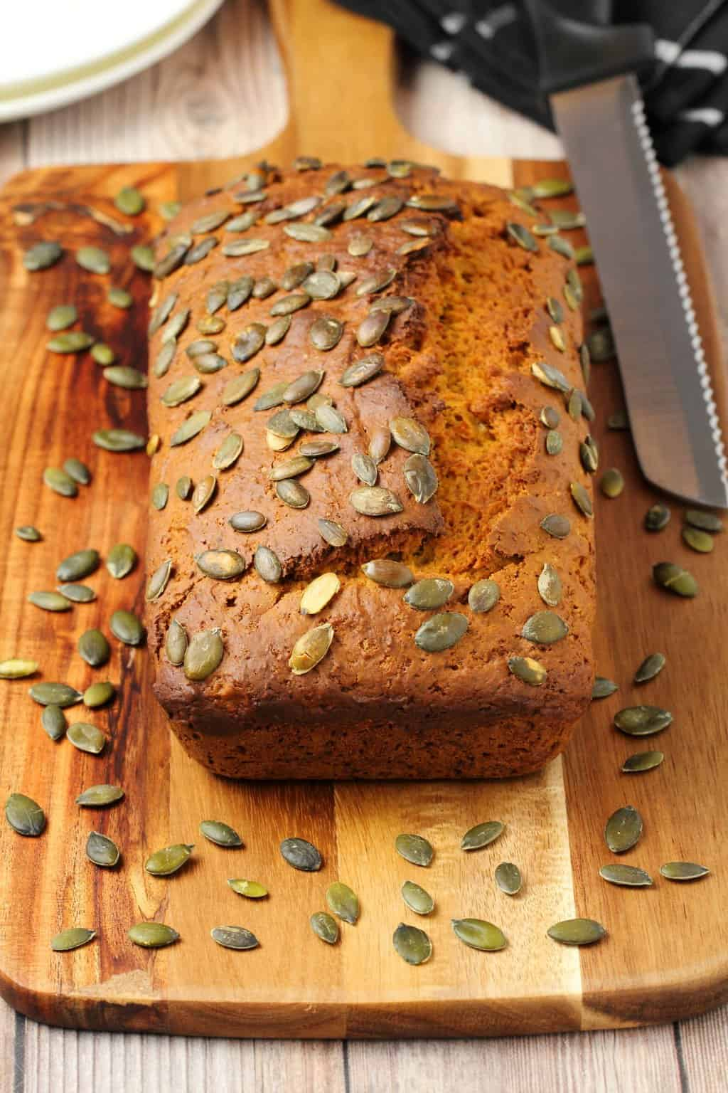 Vegan pumpkin bread topped with pumpkin seeds on a wooden board with a knife.