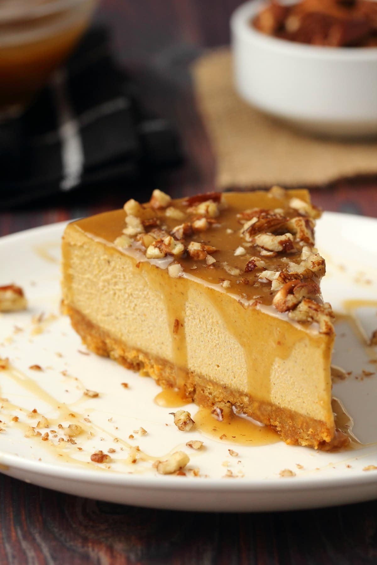 A slice of vegan pumpkin cheesecake topped with caramel sauce and crushed pecans on a white plate.