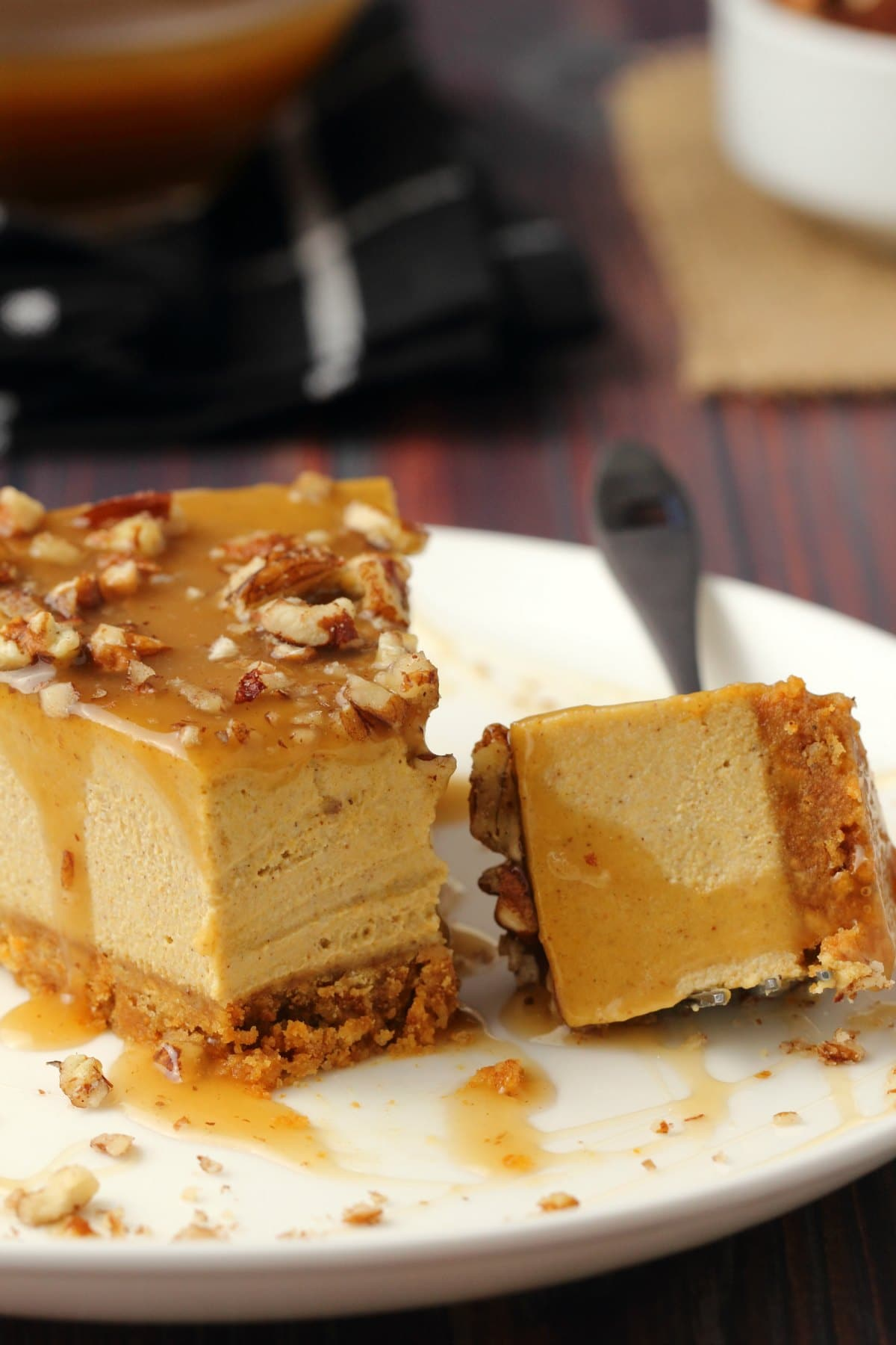 A slice of vegan pumpkin cheesecake topped with caramel sauce and crushed pecans on a white plate with a cake fork.
