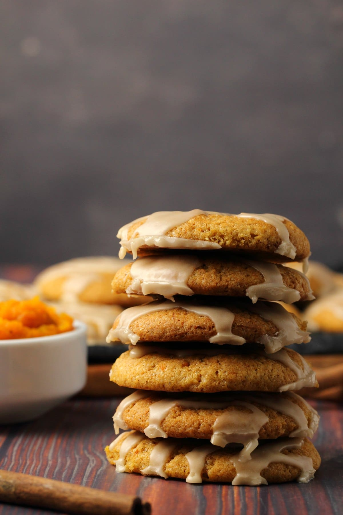 A stack of vegan pumpkin cookies topped with maple glaze.
