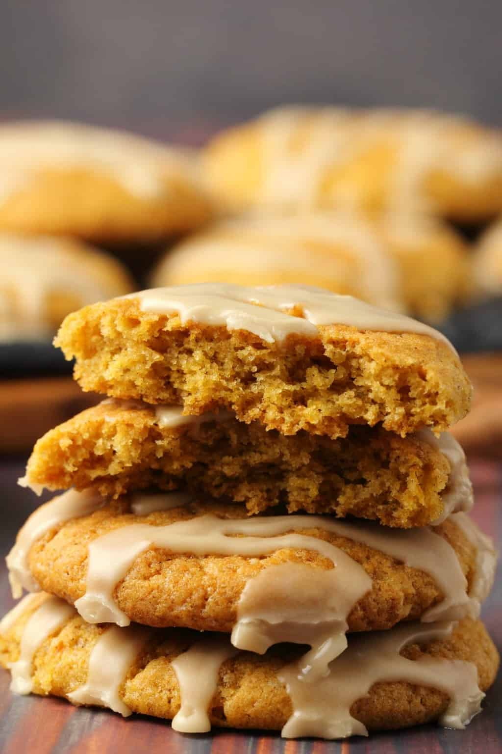 A stack of vegan pumpkin cookies topped with maple glaze, the top cookie broken in half to show the center.