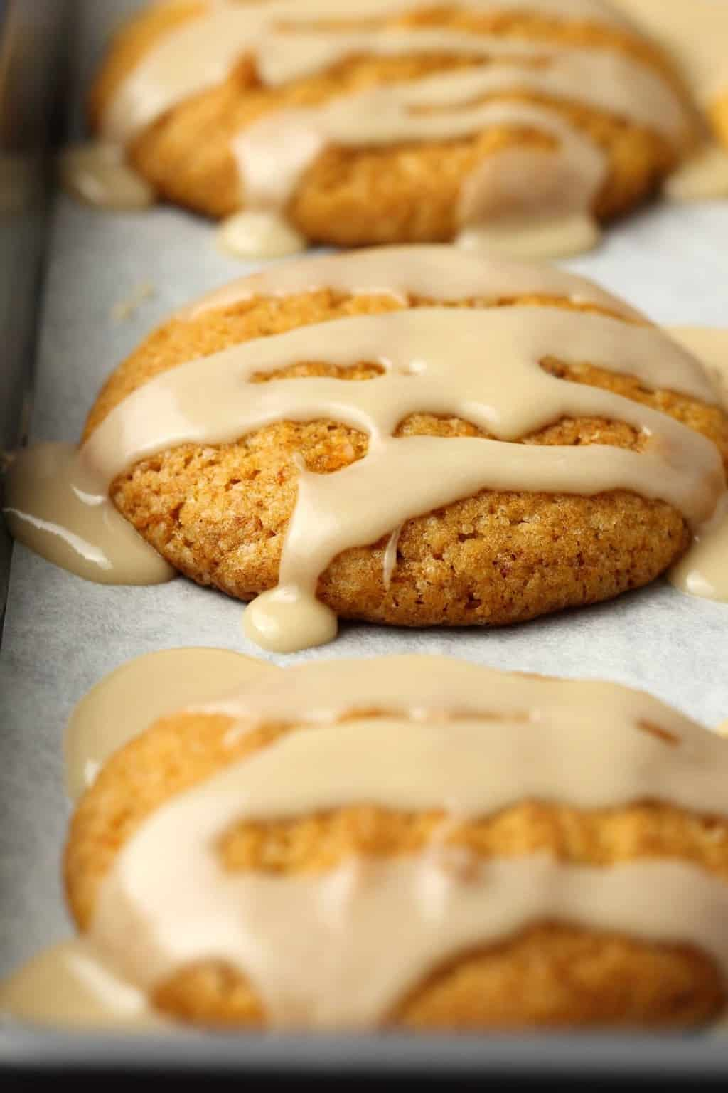 Vegan Pumpkin Cookies topped with a maple glaze on a parchment lined baking tray.