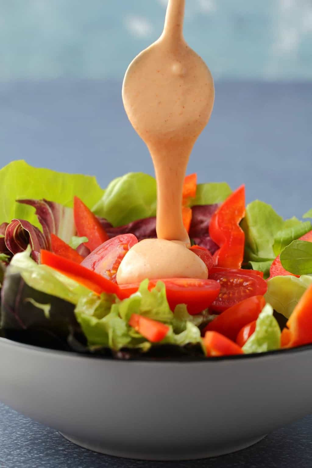 Vegan thousand island dressing pouring from a spoon onto a salad.
