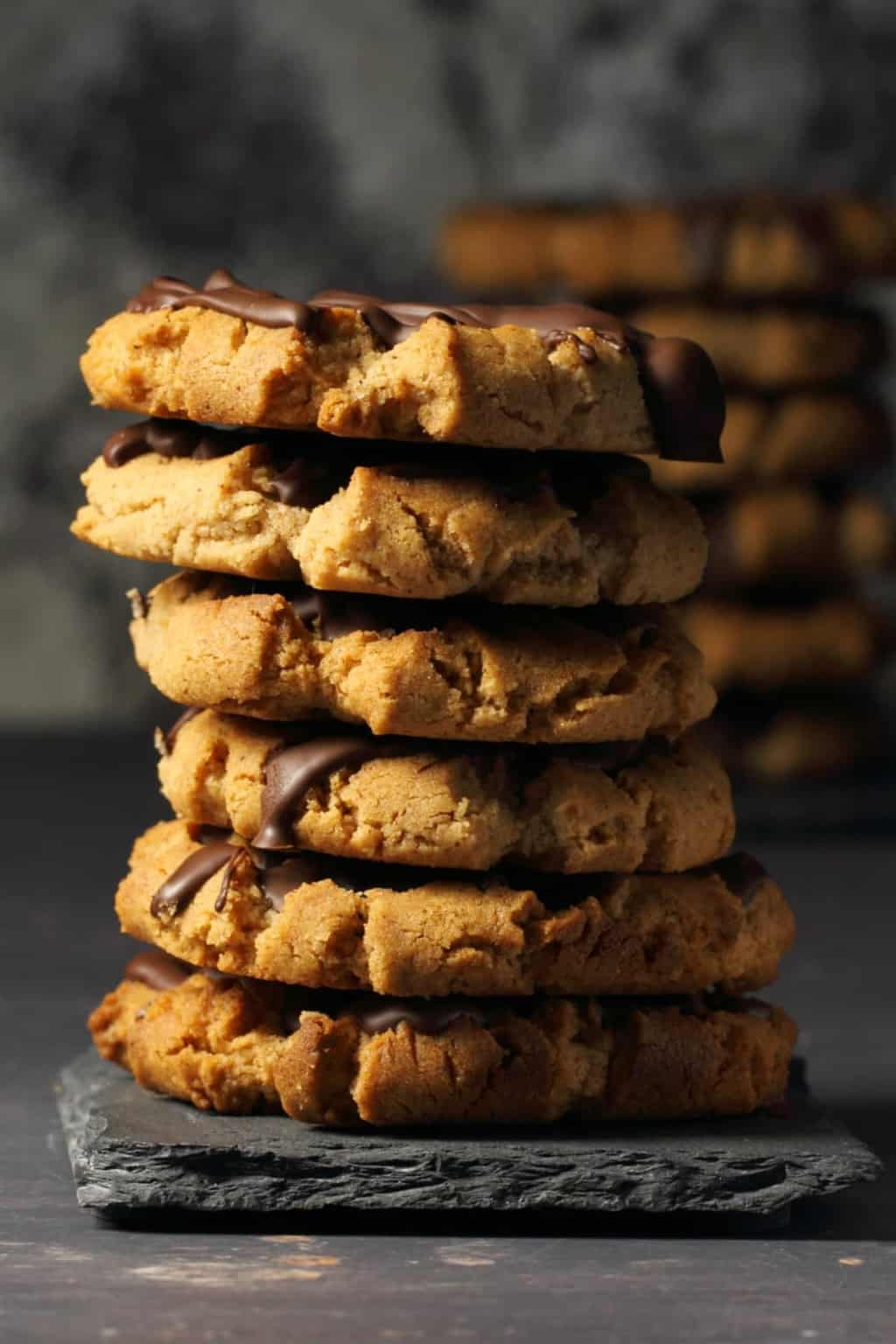 Vegan almond butter cookies topped with drizzled chocolate in a stack against a dark background.