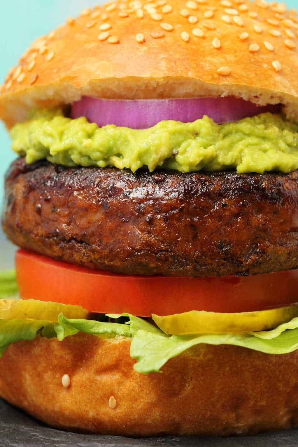 Black bean burger with burger bun, lettuce, pickles, tomato, guacamole and red onion.