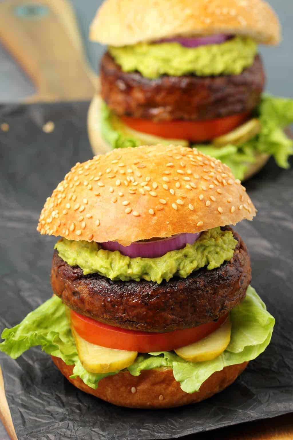 Black bean burgers on burger buns with lettuce, pickles, tomato, guacamole and red onion.