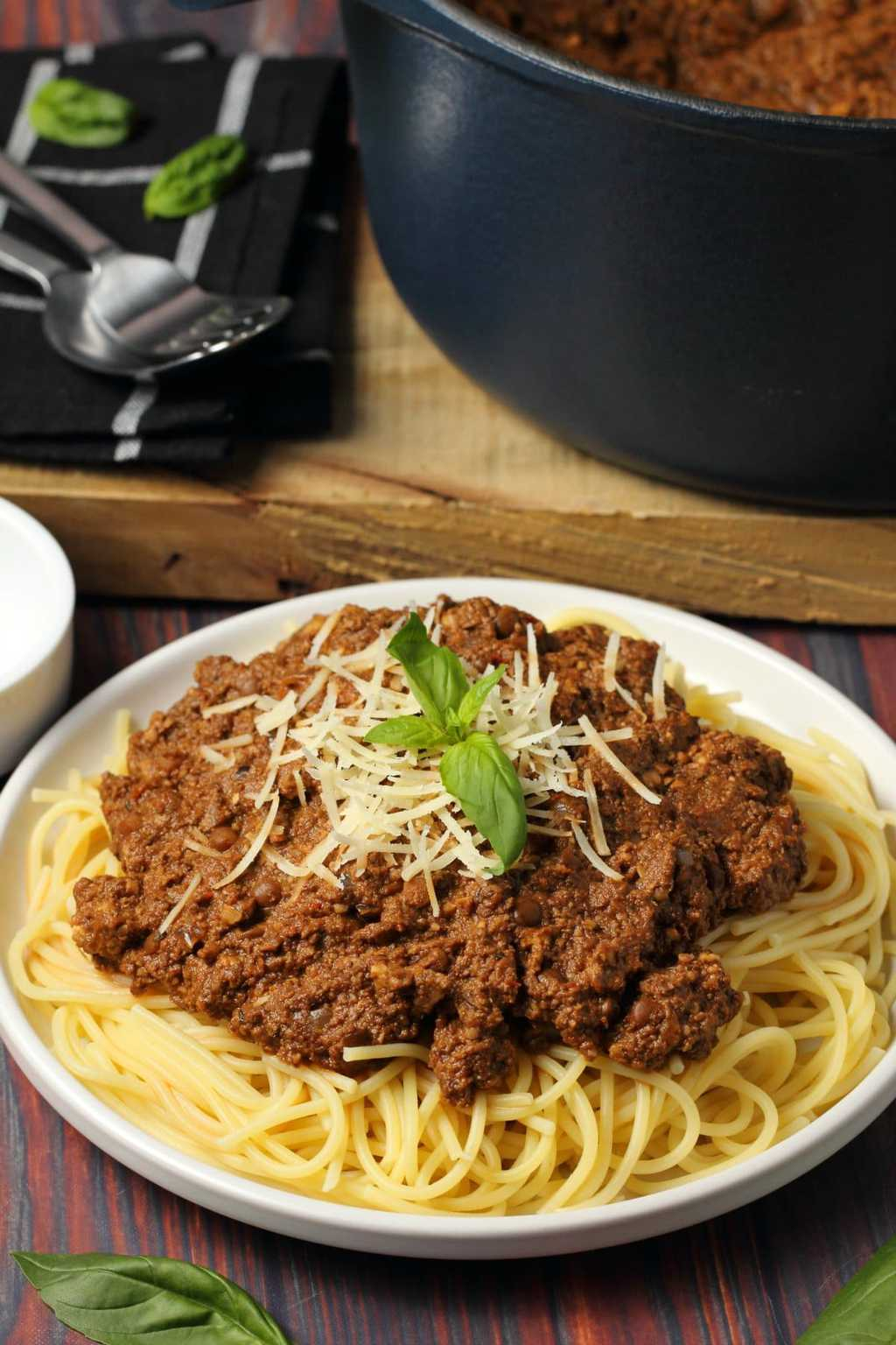 Vegan bolognese topped with fresh basil and vegan parmesan with spaghetti on a white plate.