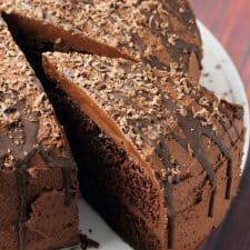 Vegan chocolate fudge cake on a white cake stand.