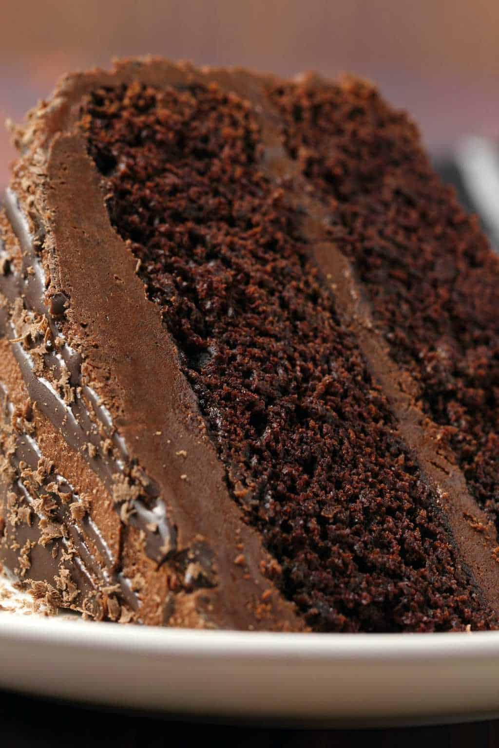 A slice of vegan chocolate fudge cake on a white plate.