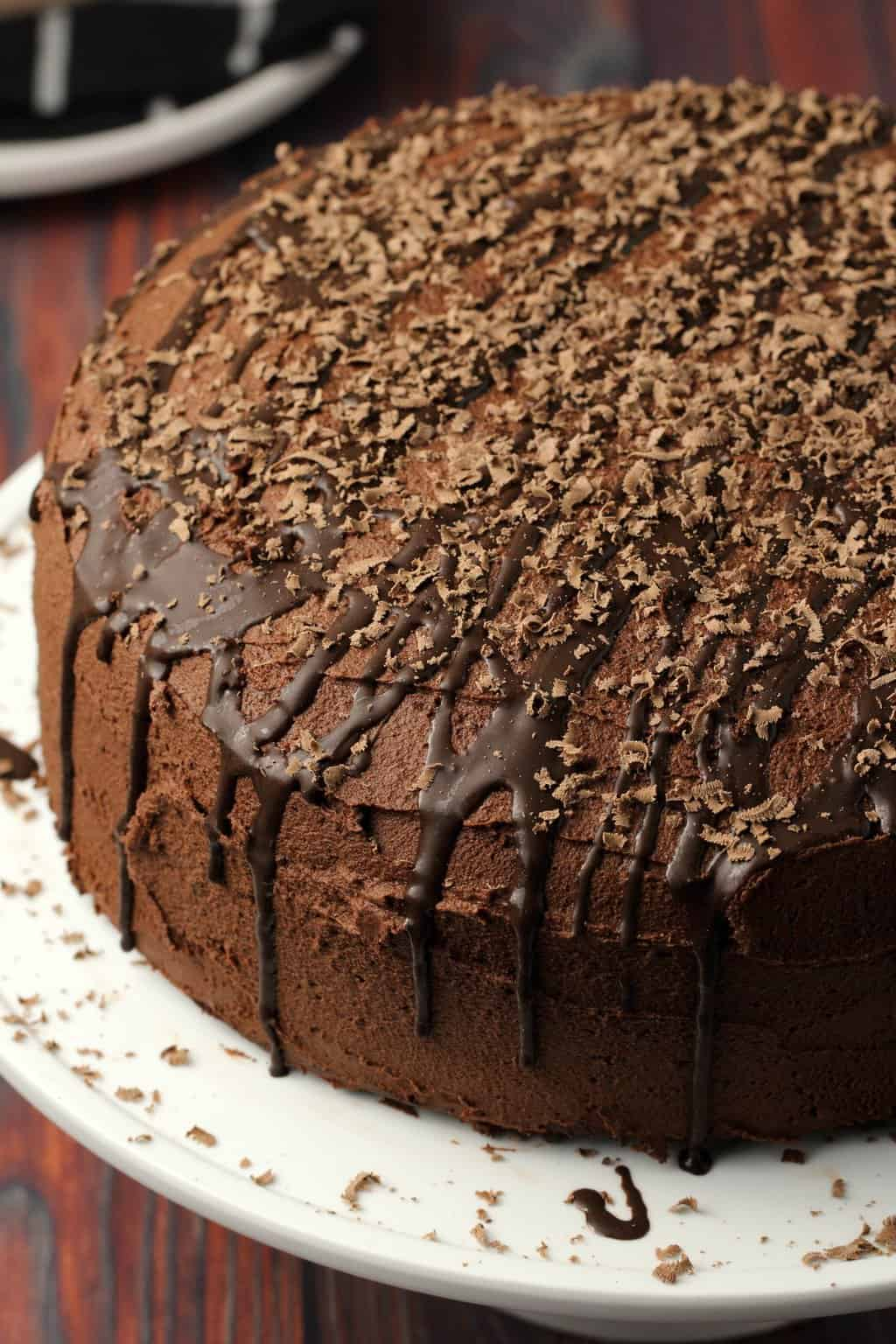 Vegan chocolate fudge cake with chocolate fudge frosting on a white cake stand.