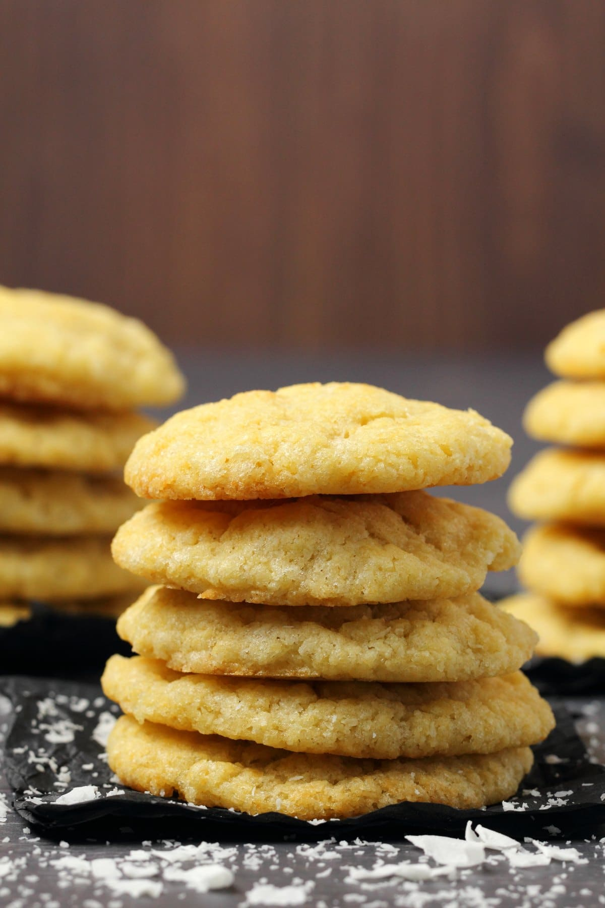 A stack of vegan coconut cookies on black tissue paper.