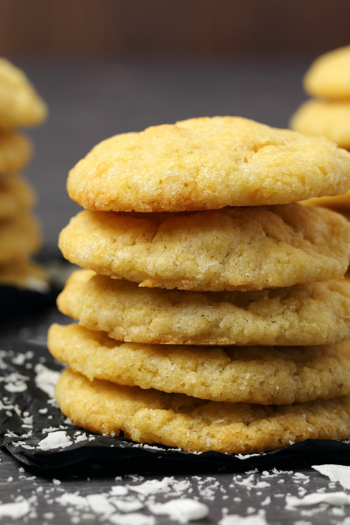 Vegan coconut cookies in a stack on black tissue paper.