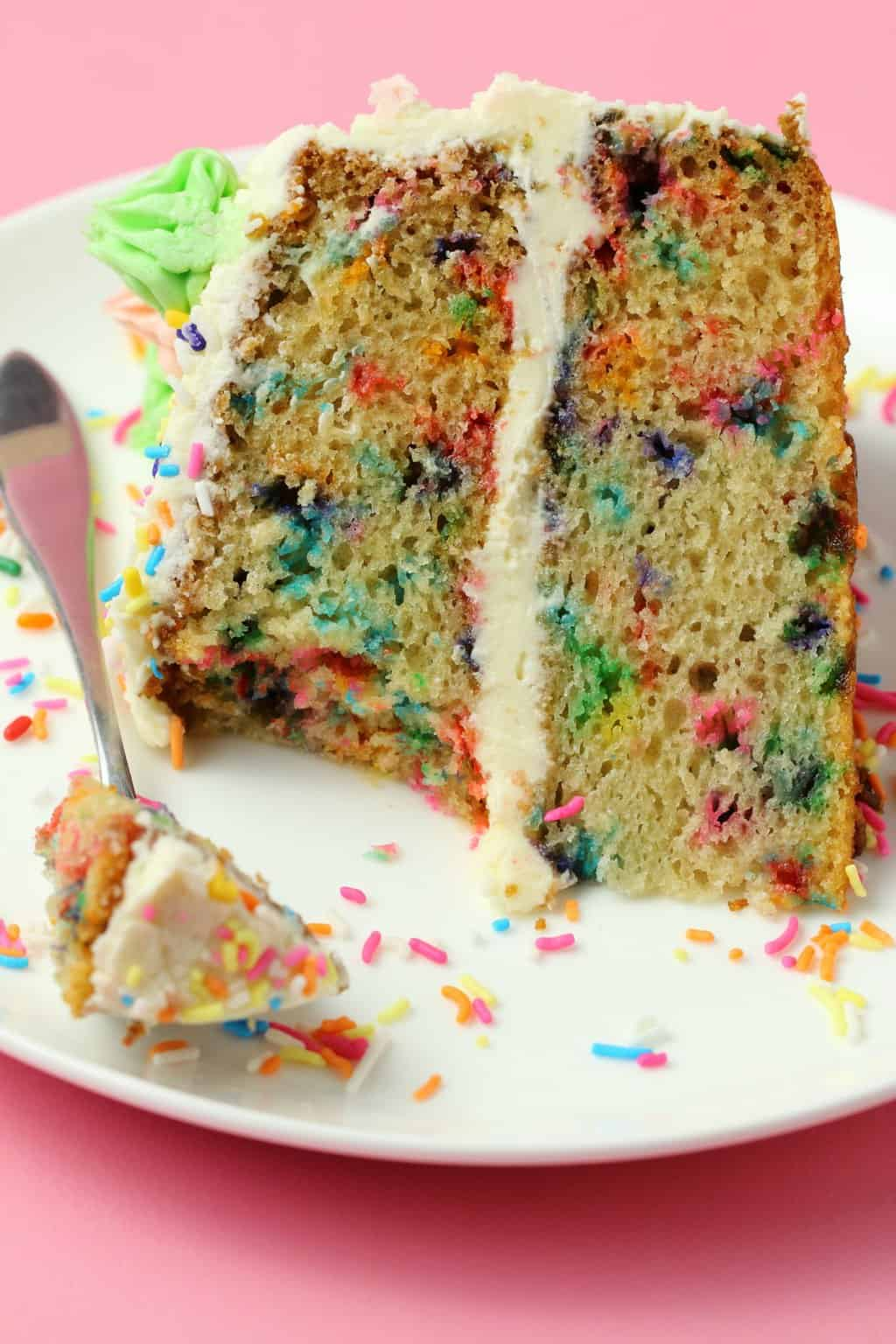 A slice of vegan funfetti cake on a white plate with a cake fork and sprinkles.