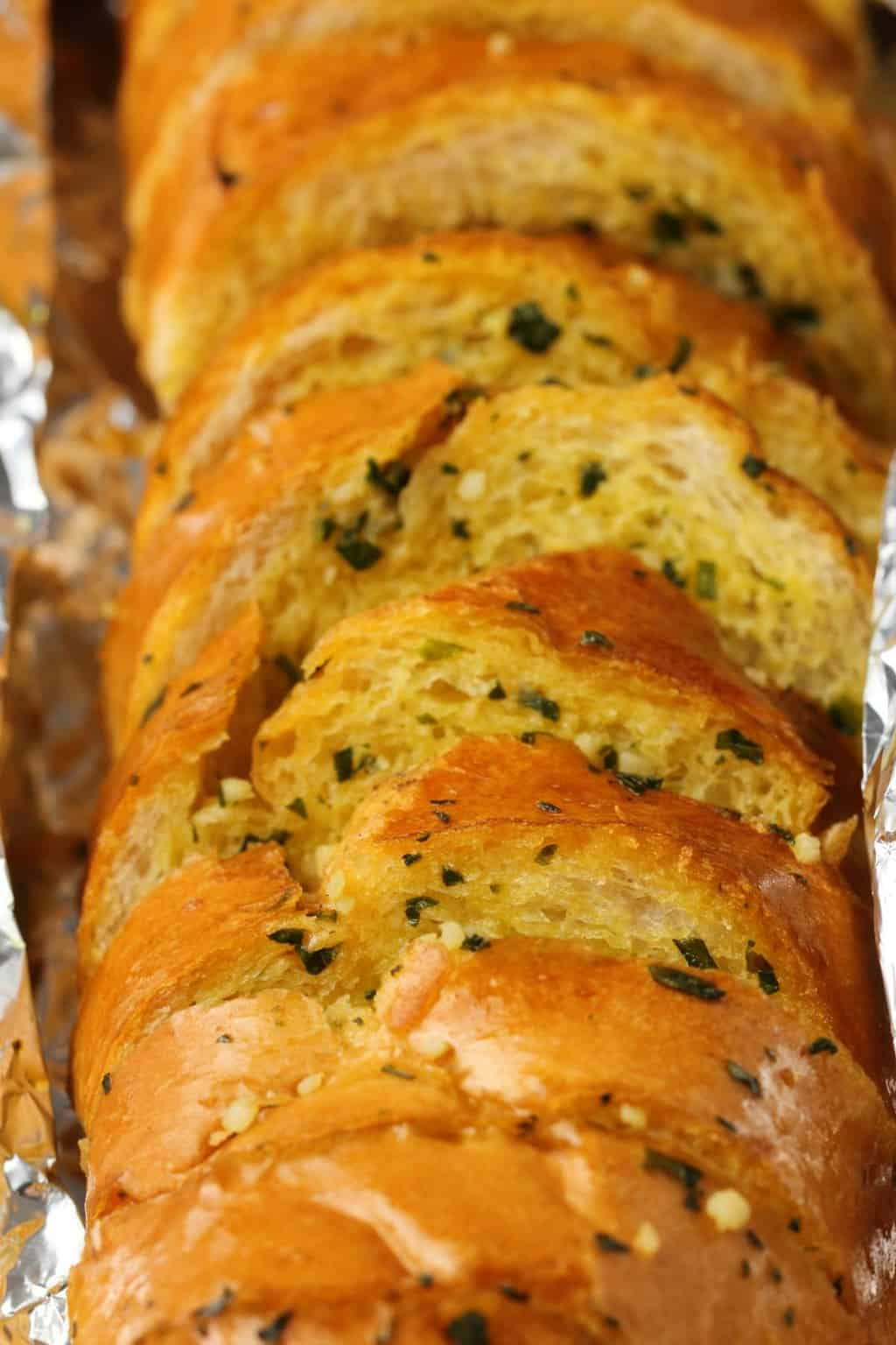 Freshly baked vegan garlic bread in tinfoil.