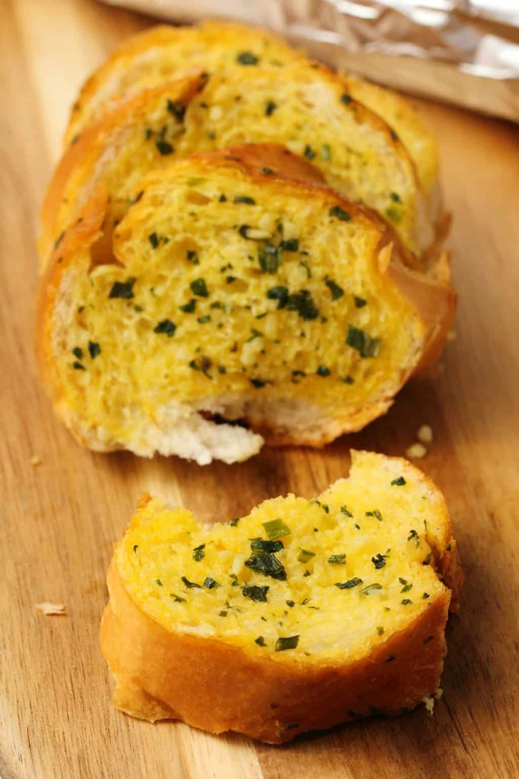 Vegan garlic bread on a wooden cutting board.