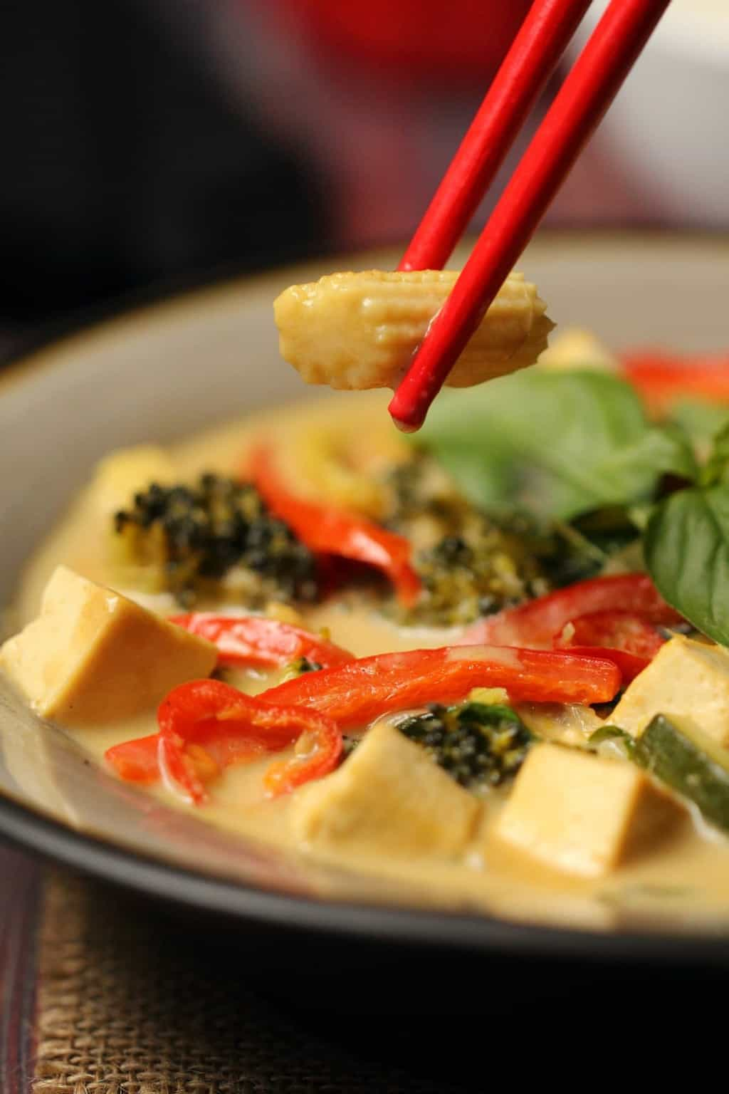 Vegan green curry in a stone bowl with red chopsticks.
