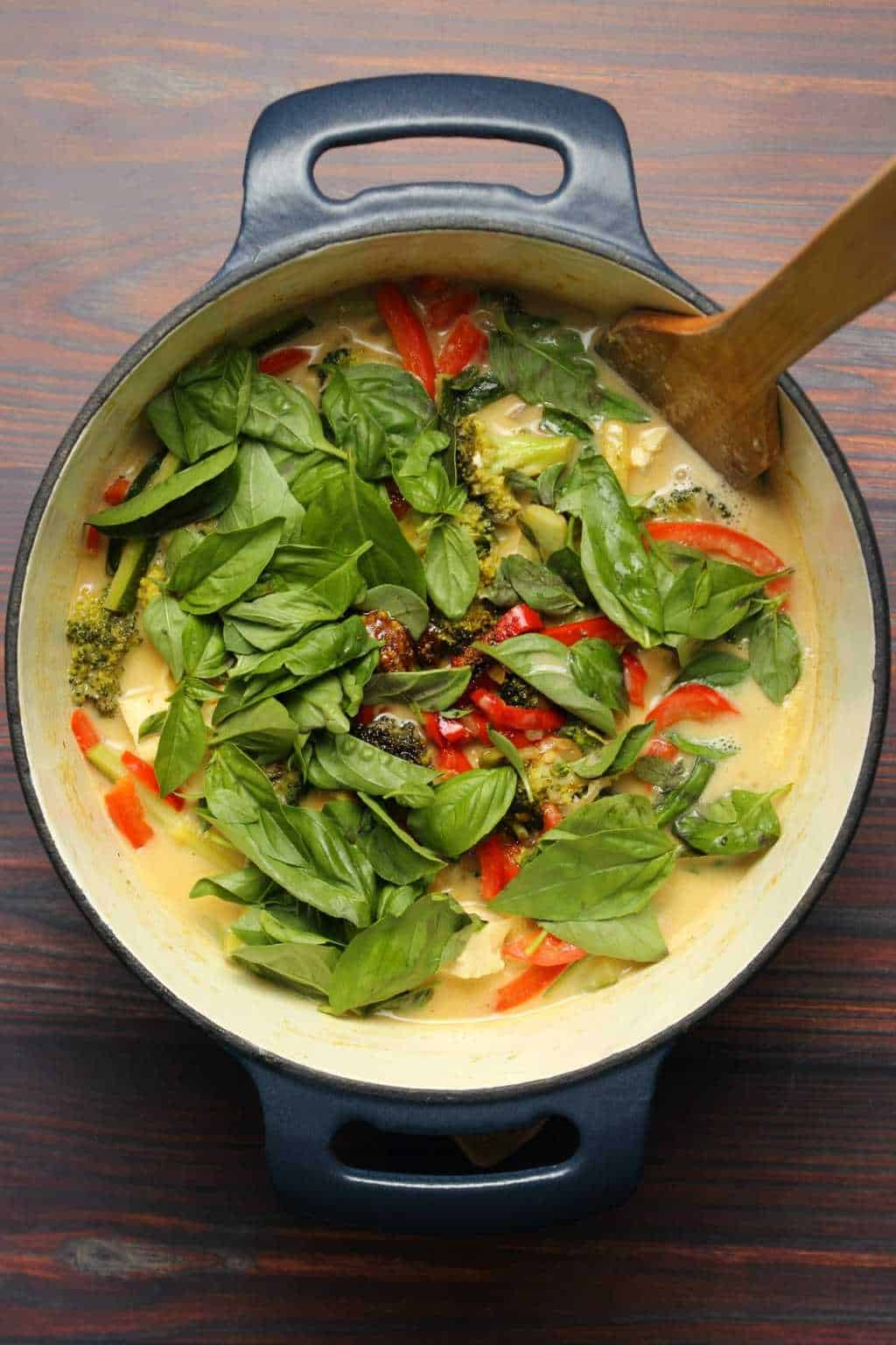 Vegan green curry in a blue cast iron pot with a wooden spoon.