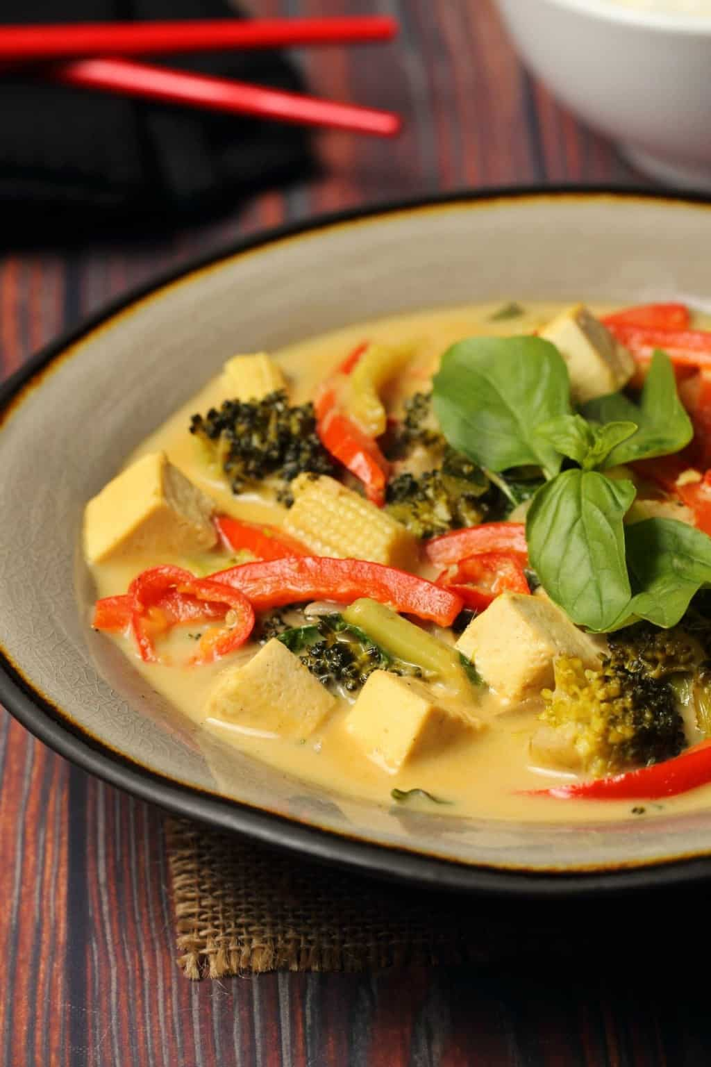 Vegan green curry topped with fresh basil in a stone bowl.