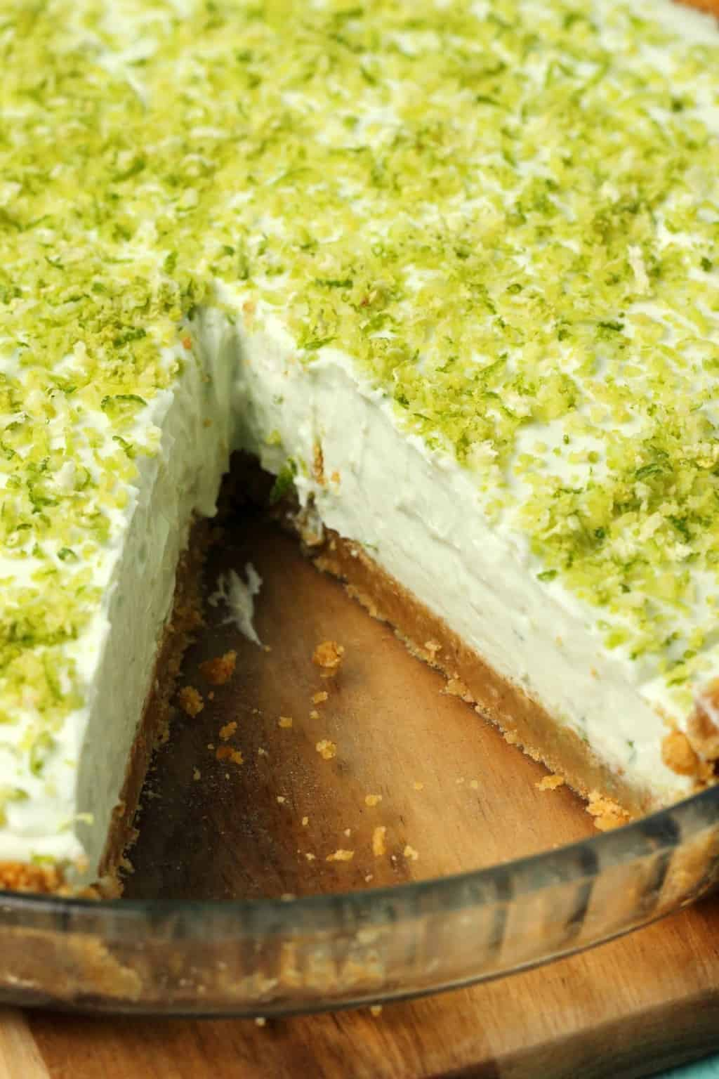 Vegan key lime pie topped with lime zest in a glass pie dish.