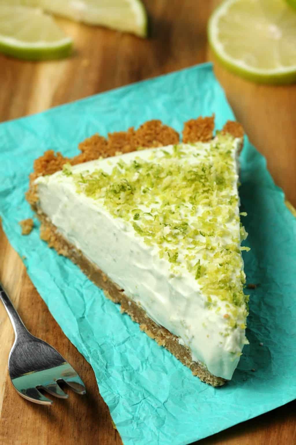 A slice of vegan key lime pie on a blue napkin.