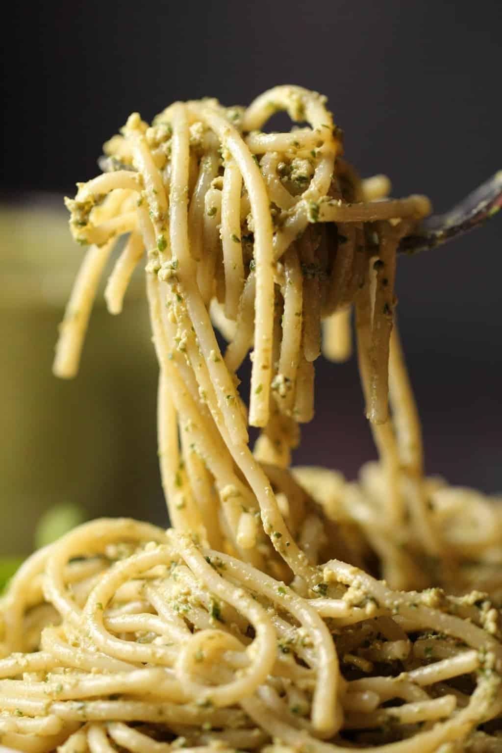 Vegan pesto mixed with spaghetti on a fork.