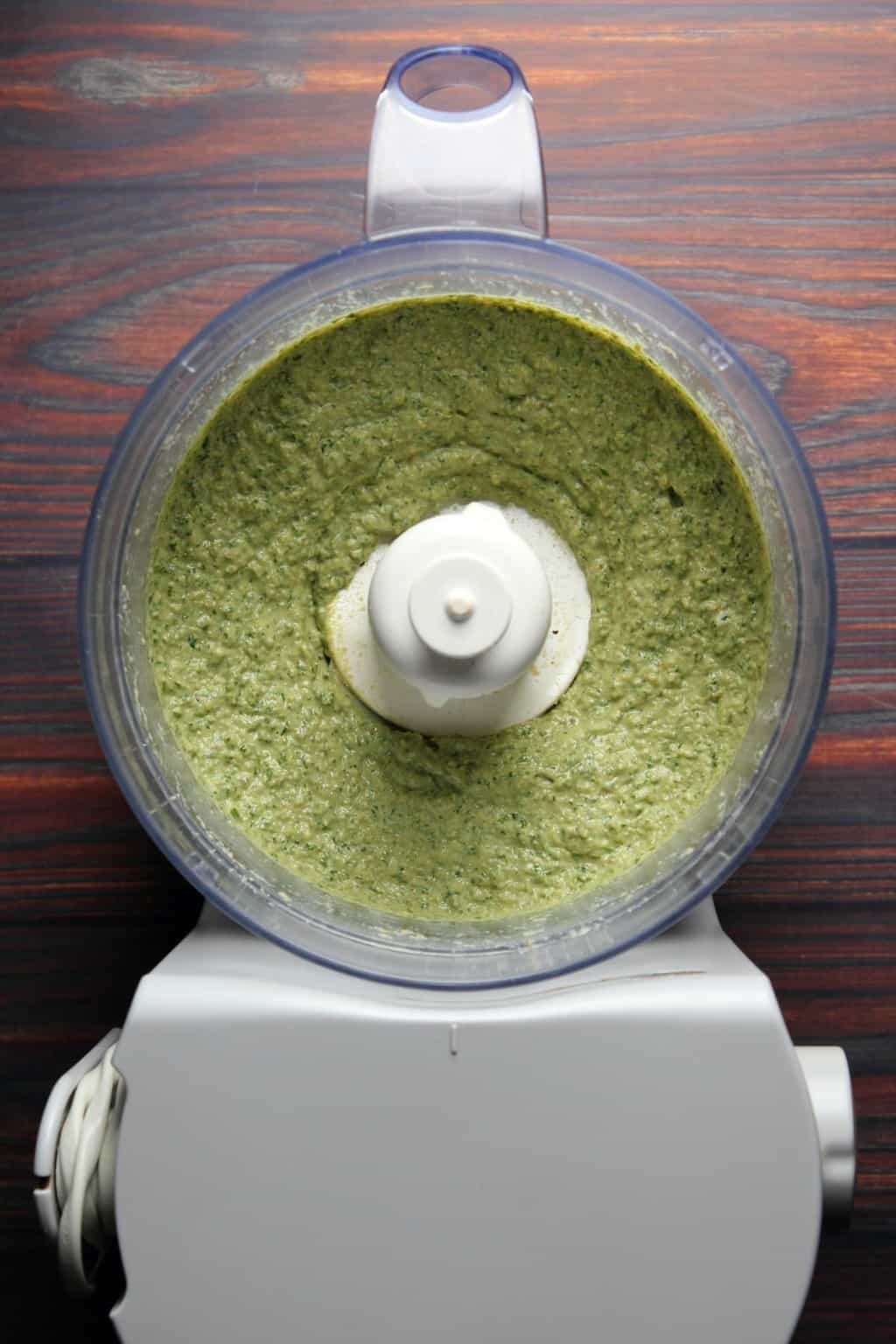 Freshly made vegan pesto in a food processor.