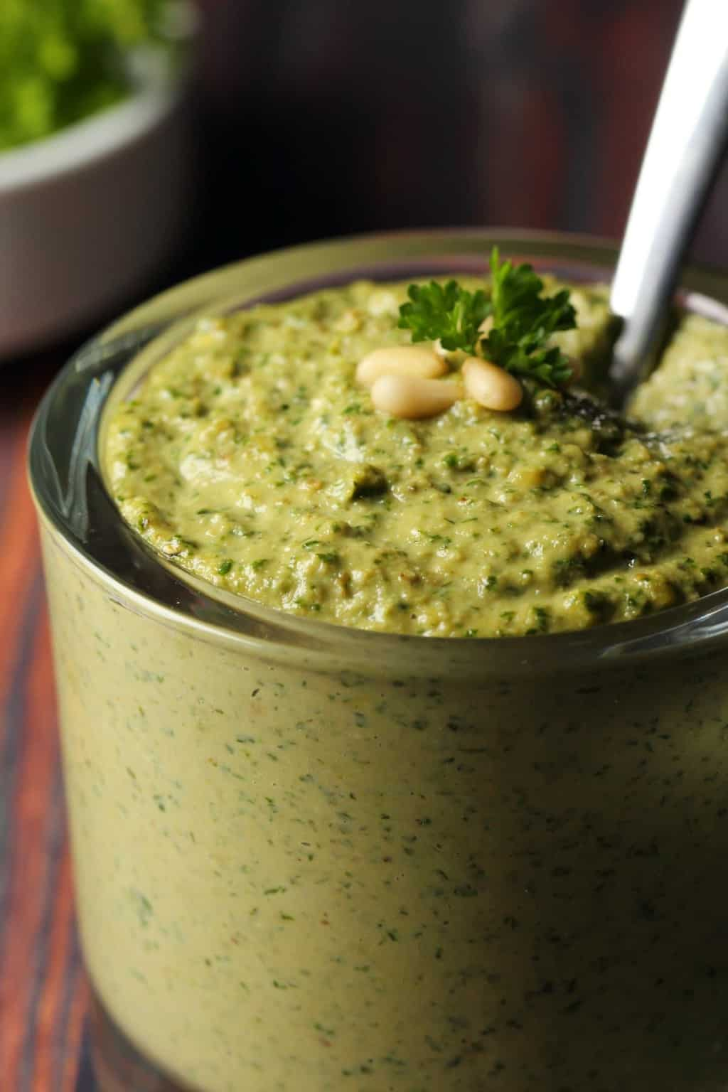 Vegan pesto in a glass jar with a spoon.