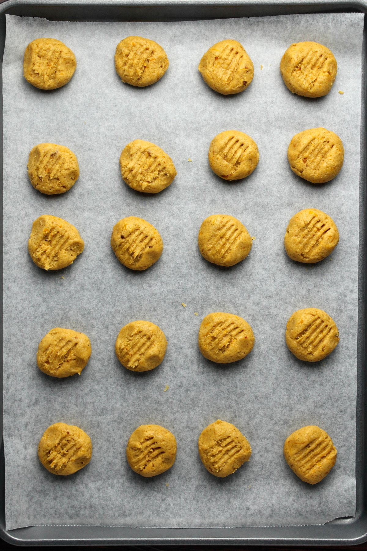 Pumpkin cookies on a parchment lined baking tray ready to go into the oven.