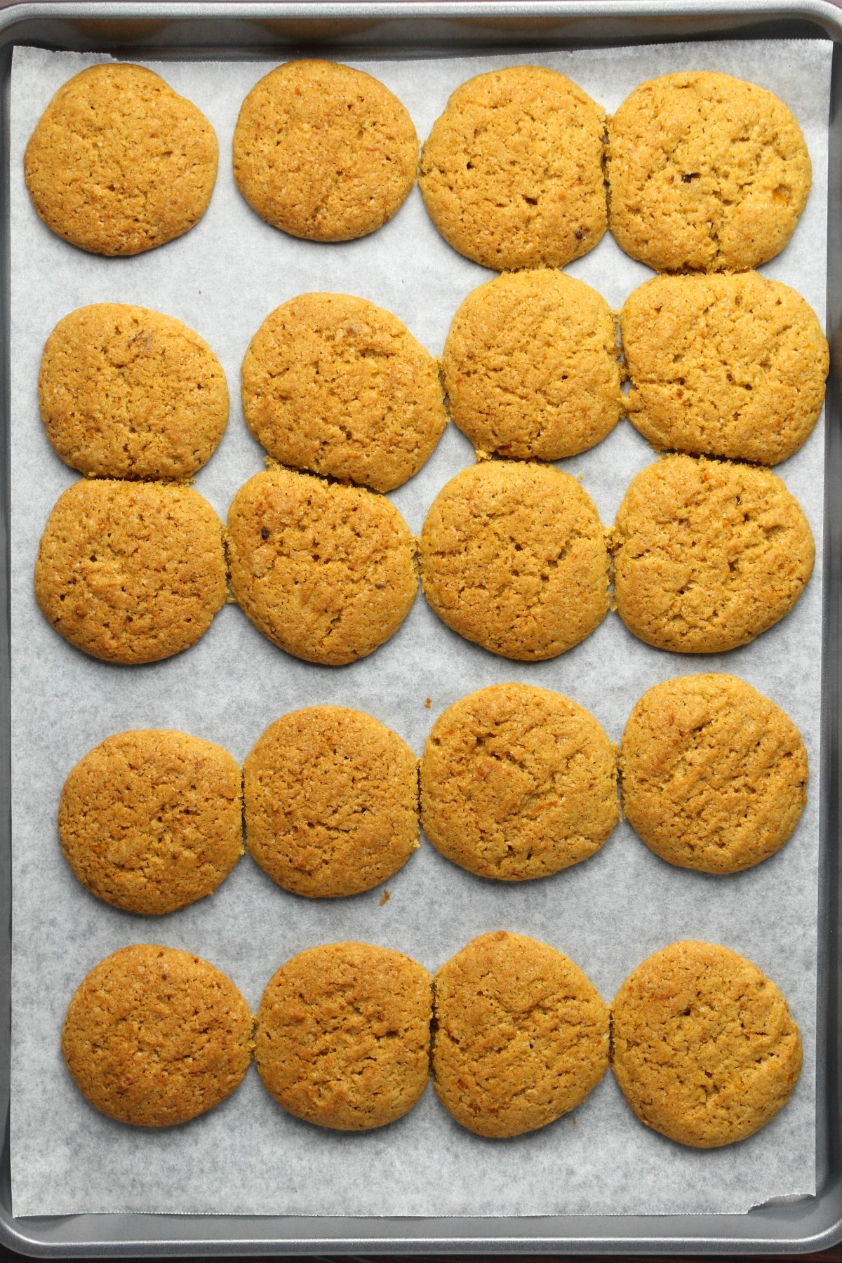 Freshly baked pumpkin cookies on a parchment lined baking tray.