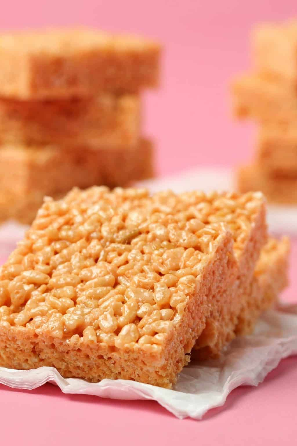 Vegan rice krispie treats in a row on white tissue paper.