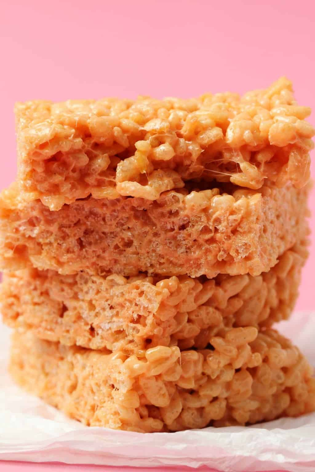 Vegan rice krispie treats stacked up on top of each other, the top square broken in half to show the center.