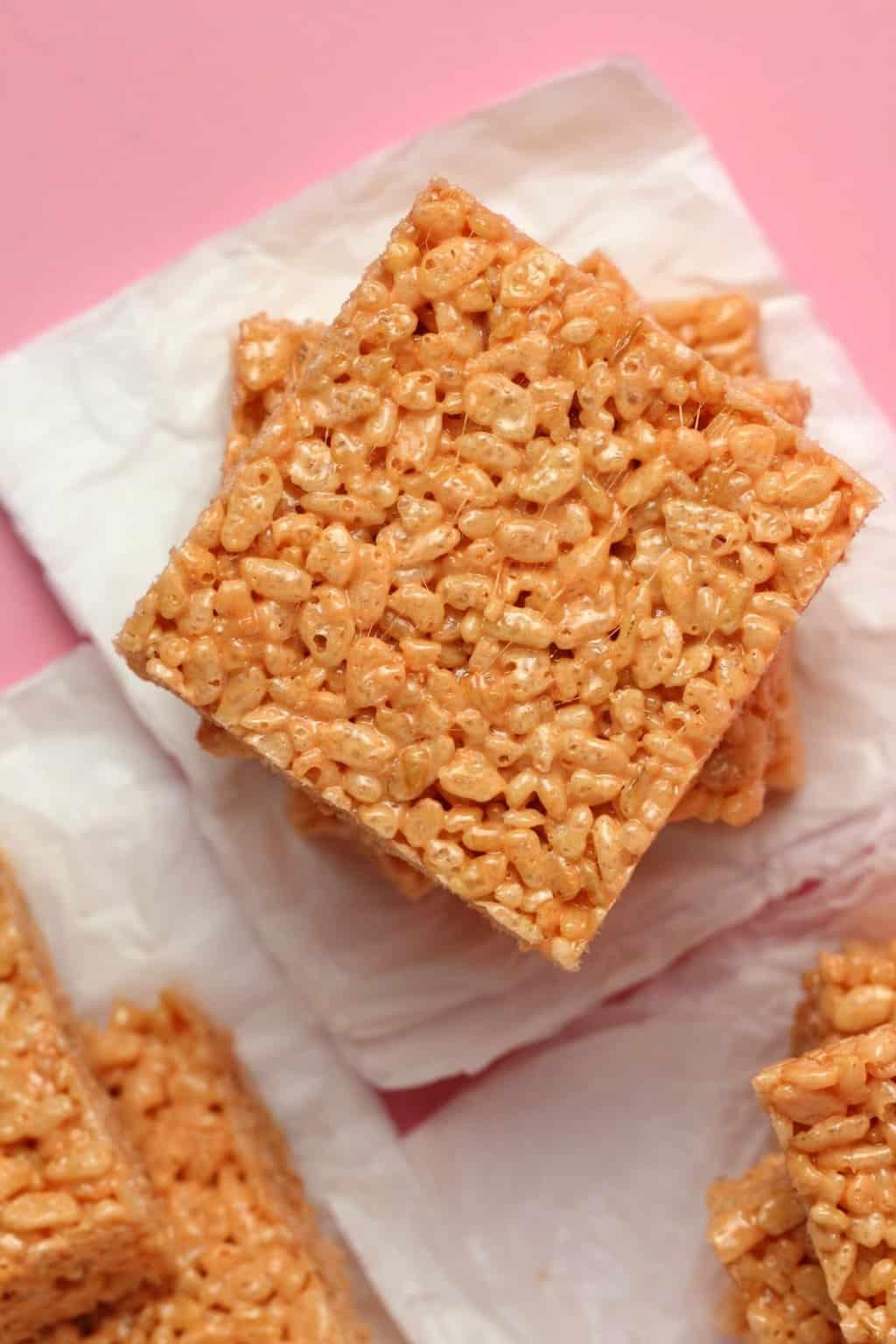 Vegan rice krispie treats in a stack on white tissue paper.