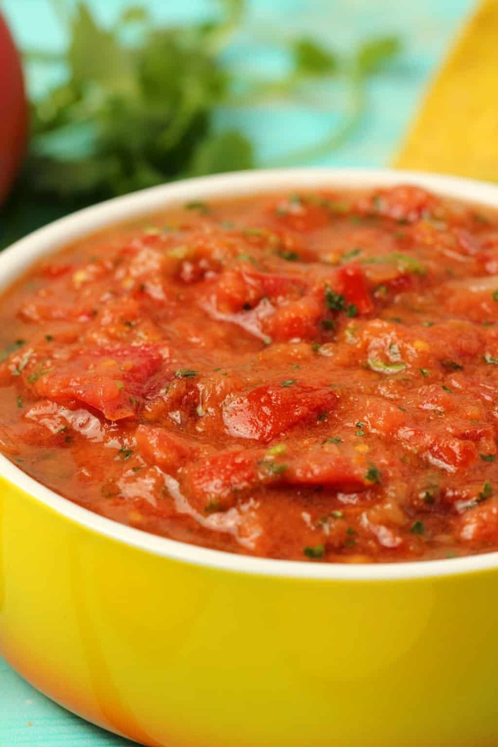 Homemade salsa in a yellow and white glass dish.