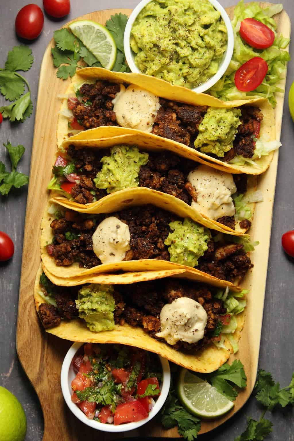 Vegan taco meat in tacos with shredded lettuce, salsa, guacamole and vegan sour cream on a wooden board.