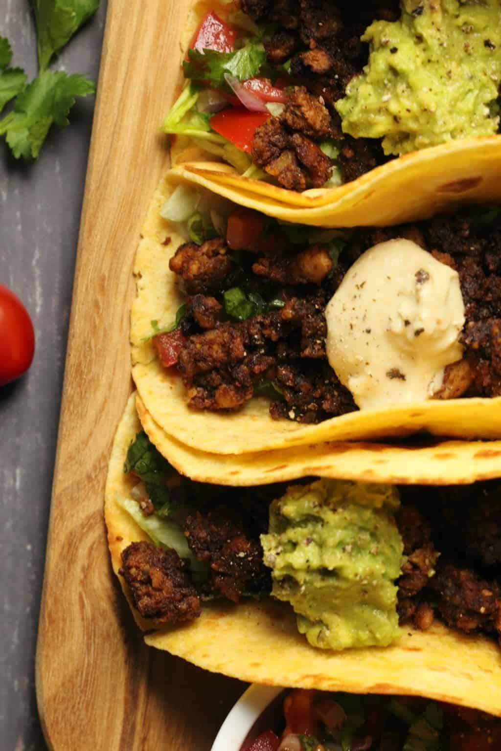 Vegan taco meat in tacos with lettuce, salsa, guacamole and vegan sour cream on a wooden board.