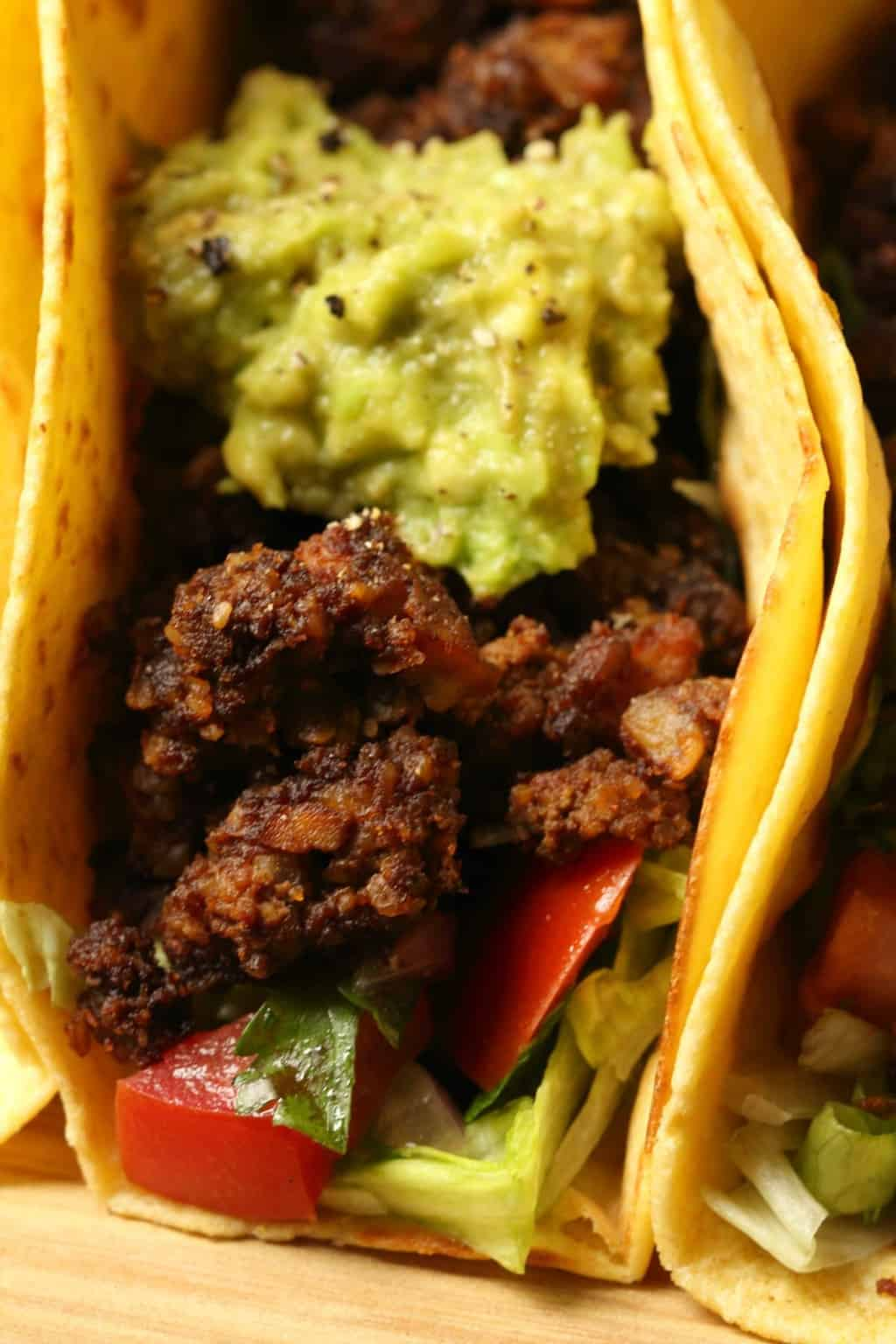 Vegan taco meat in a taco with lettuce, salsa and guacamole.
