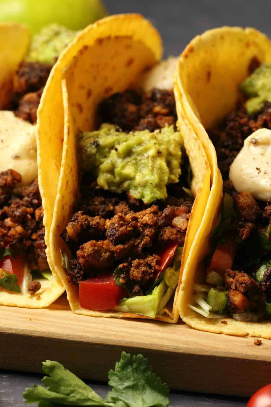 Vegan taco meat in tacos with lettuce, salsa, guacamole and vegan sour cream, on a wooden board.
