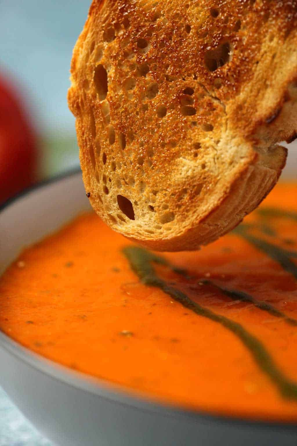 A slice of toasted bread about to dip into a bowl of vegan tomato basil soup.