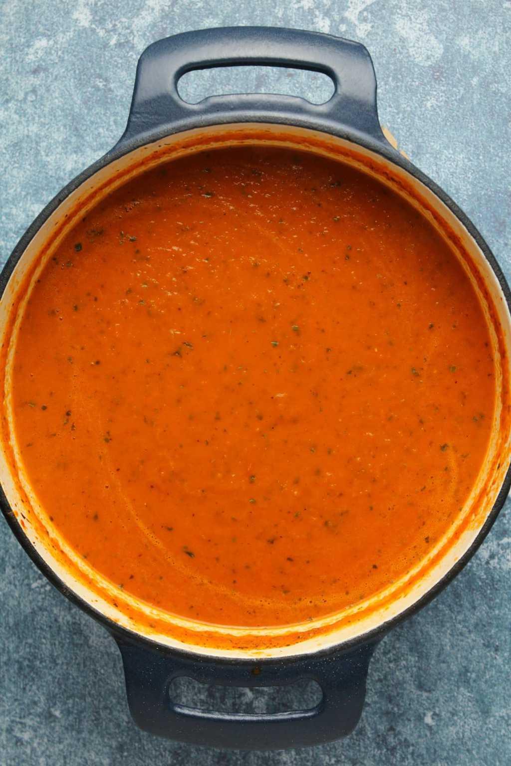 Vegan tomato basil soup in a cast iron pot.