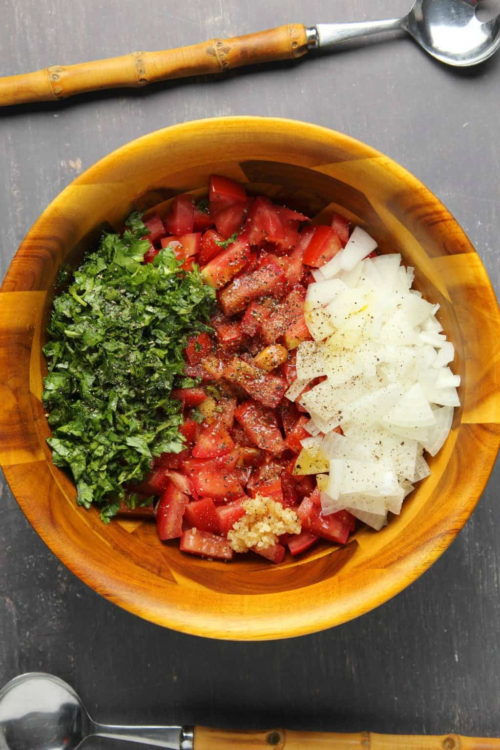 Ingredients for pico de gallo in a wooden bowl ready to be mixed up.