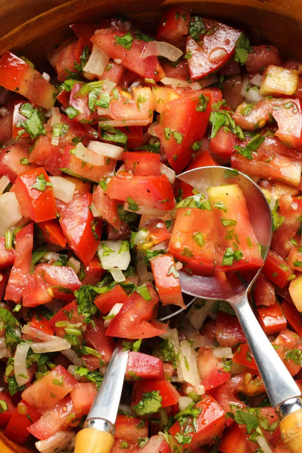 Pico de gallo in a wooden bowl with spoons.